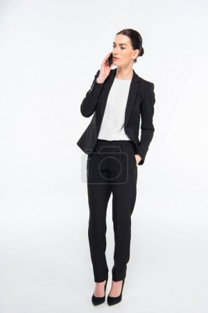 Photo pour Serious young businesswoman talking on smartphone isolated on white - image libre de droit
