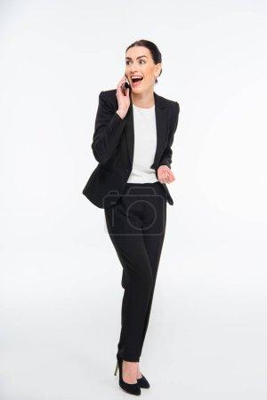 Foto de Excited professional businesswoman talking on smartphone isolated on white - Imagen libre de derechos