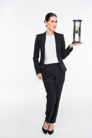 Photo pour Femme d'affaires souriante tenant sablier et regardant la caméra isolée sur blanc - image libre de droit