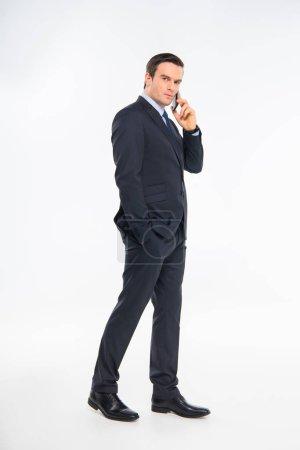 Foto de Serious young businessman talking on smartphone isolated on white - Imagen libre de derechos