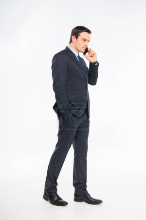 Photo for Serious young businessman in suit talking on smartphone isolated on white - Royalty Free Image