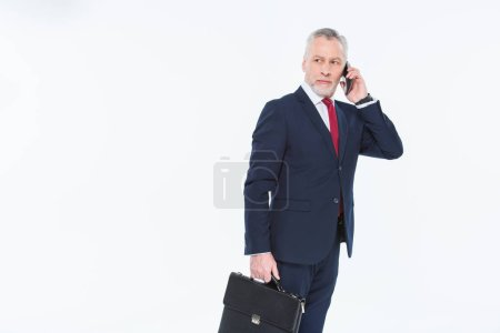 Foto de Handsome mature businessman holding briefcase and using smartphone isolated on white - Imagen libre de derechos