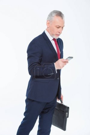Photo pour Handsome mature businessman holding briefcase and using smartphone isolated on white - image libre de droit