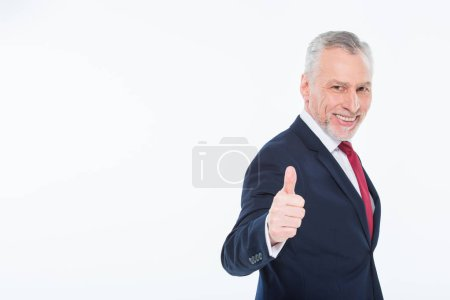 Foto de Handsome mature businessman showing thumb up isolated on white - Imagen libre de derechos