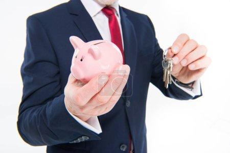 Businessman holding keys and piggy bank