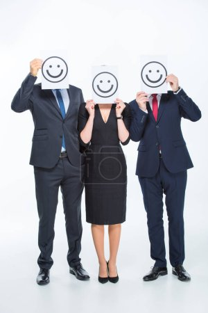 Photo for Three businesspeople holding cards with smileys isolated on white - Royalty Free Image