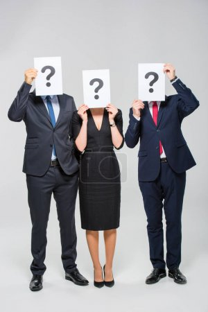 Photo for Three businesspeople holding cards with question marks - Royalty Free Image