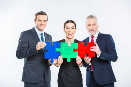 Photo for Three happy businesspeople holding puzzle pieces and looking at camera isolated on white - Royalty Free Image
