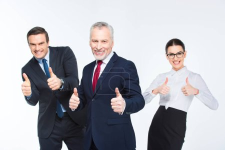 Foto de Three happy business people showing thumbs up isolated on white - Imagen libre de derechos