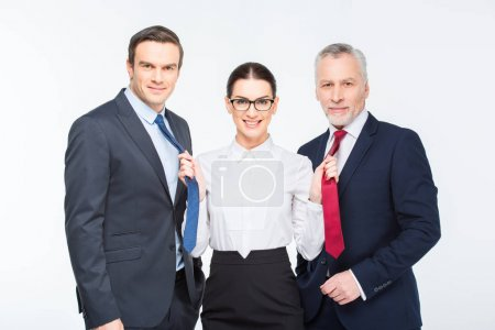 Photo for Three happy business people standing and woman holding neckties of businessmen isolated on white - Royalty Free Image