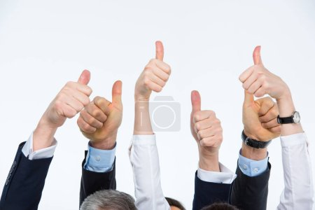 Foto de Partial view of hands of businesspeople showing thumbs up isolated on white - Imagen libre de derechos