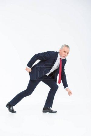 Photo pour Homme d'affaires mature en costume prêt à courir isolé sur blanc - image libre de droit