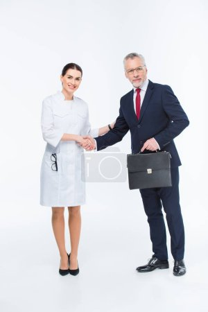 Photo for Two businesspeople shaking hands looking at camera isolated on white - Royalty Free Image