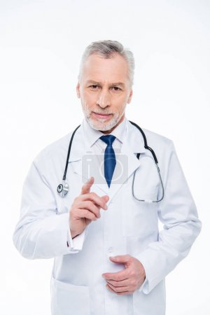 Photo pour Smiling mature male doctor with stethoscope pointing with finger isolated on white - image libre de droit