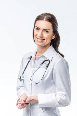 Photo pour Beautiful female doctor with stethoscope smiling at camera isolated on white - image libre de droit