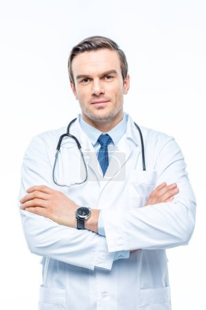 Photo pour Confident male doctor with stethoscope and crossed arms isolated on white - image libre de droit