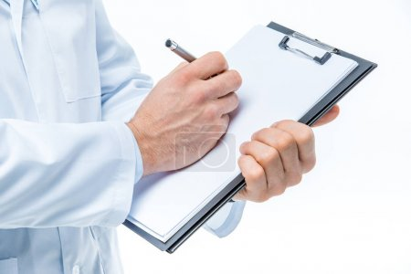 Photo for Close-up partial view of male doctor holding clipboard and writing on white blank paper isolated on white - Royalty Free Image