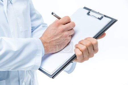 Photo pour Close-up partial view of male doctor holding clipboard and writing on white blank paper isolated on white - image libre de droit