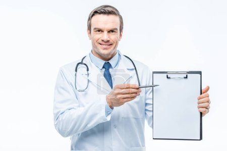 Photo pour Smiling male doctor holding clipboard and pointing with pen at copy space isolated on white - image libre de droit