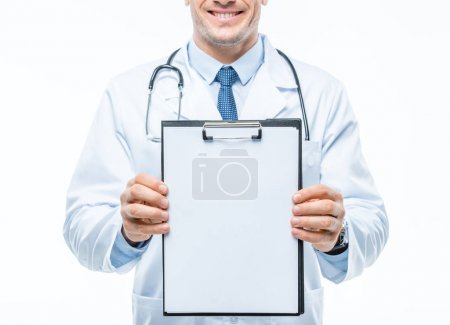 Photo for Partial view of smiling male doctor holding clipboard isolated on white - Royalty Free Image