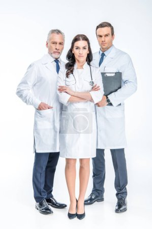 Photo for Full length portrait of three confident doctors looking at camera isolated on white - Royalty Free Image