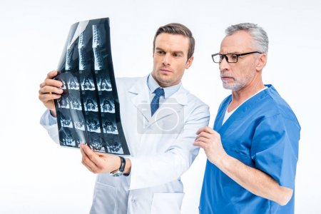 Photo for Two male doctors examining x-ray image isolated on white - Royalty Free Image