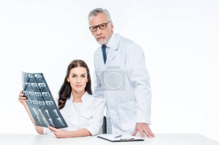 Photo for Two doctors with x-ray image looking at camera isolated on white - Royalty Free Image