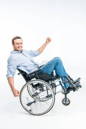 Photo pour Happy handicapped man in wheelchair looking at camera isolated on white - image libre de droit
