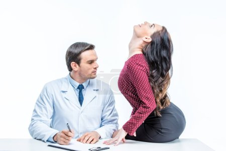 Photo for Young woman sitting on table and seducing handsome male doctor isolated on wite - Royalty Free Image