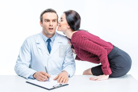 Photo for Young seductive woman sitting on table and whispering in ear of surprised male doctor isolated on white - Royalty Free Image