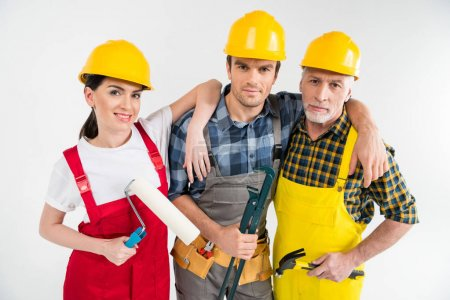 Photo pour Professional construction workers holding tools and looking at camera isolated on white - image libre de droit
