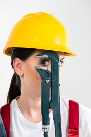 Female builder holding wrench