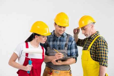 Foto de Group of professional male and female construction workers looking at clipboard  isolated on white - Imagen libre de derechos