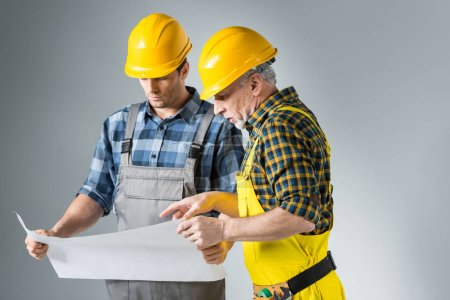 Photo for Two professional male engineers working with blueprint  isolated on grey - Royalty Free Image