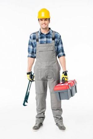 Photo for Smiling workman in hard hat holding tool kit and looking at camera  isolated on white - Royalty Free Image