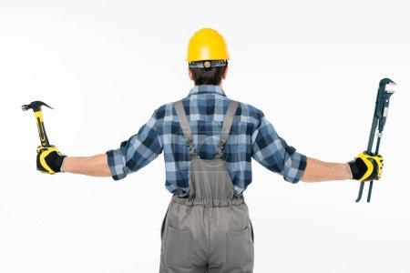 Photo pour Vue arrière de l'ouvrier retenant le marteau et la clé de pipe d'isolement sur le blanc - image libre de droit