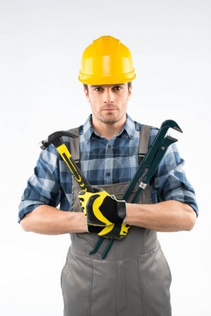 Workman holding hammer and pipe wrench