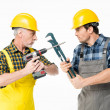 Two male construction workers fighting with tools ...