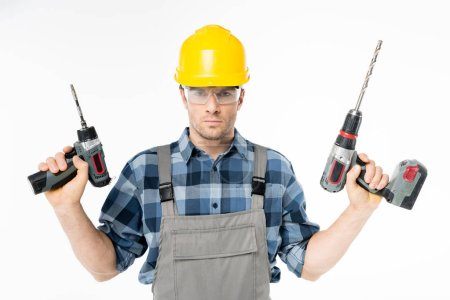 Photo for Serious workman in protective workwear holding electric drills isolated on white - Royalty Free Image