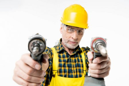 Photo for Close-up view of mature workman holding electric drills and looking at camera isolated on white - Royalty Free Image