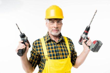 Photo pour Souriant homme mûr en tenue de travail de protection tenant des perceuses électriques isolées sur blanc - image libre de droit