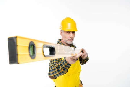 Photo for Mature workman in yellow hard hat holding level tool  isolated on white - Royalty Free Image