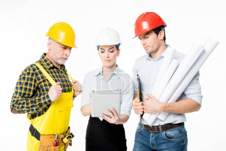 Foto de Two architects and mature workman looking at digital tablet isolated on white - Imagen libre de derechos