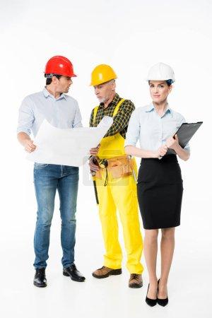 Foto de Arquitecta sonriendo mientras sus colegas examinan planos aislados en blanco - Imagen libre de derechos