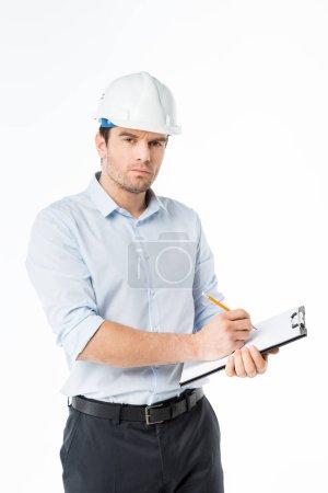 Photo pour Architecte masculin confiant en casque dur prenant des notes dans le presse-papiers isolé sur blanc - image libre de droit