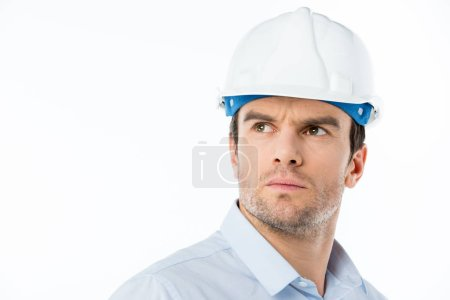 Photo for Pensive male architect in hard hat looking at distance isolated on white - Royalty Free Image