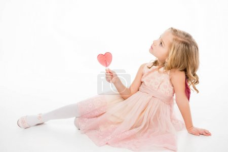 Photo for Cute little girl in pink dress holding heart shaped lollipop isolated on white - Royalty Free Image