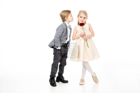Foto de Cute little boy and girl on date. Girl holding fresh red rose flower isolated on white - Imagen libre de derechos