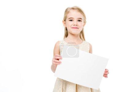 Photo pour Souriante petite fille tenant une carte blanche et regardant la caméra isolée sur blanc - image libre de droit