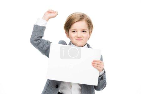 Photo pour Petit garçon confiant tenant la carte blanche et levant le poing isolé sur blanc - image libre de droit